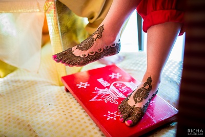Intricately designed mehendi on the bride's feet featuring peacock inspired patterns