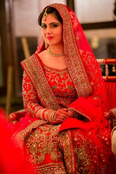 Deep red heavily embellished wedding attire styled with minimum polki studded gold jewellery
