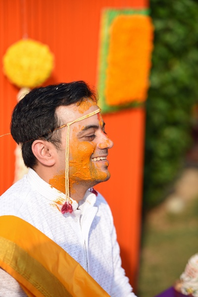 The groom is all smiles during his haldi ceremony prior to the wedding.