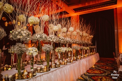 Table decorated with baby's breath, yellow Roses and white Carnations bunched into glass vases