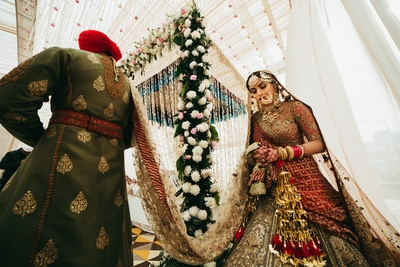 An interesting shot of the bride and groom taking pheras at the wedding ceremony