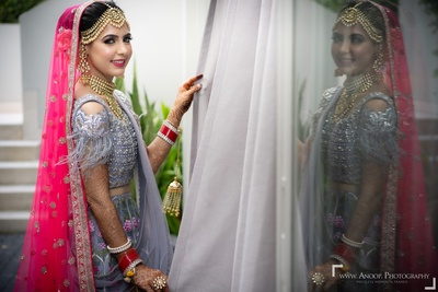 The bride looks stunning in this greyish-blue lehenga paired with a fuschia dupatta.