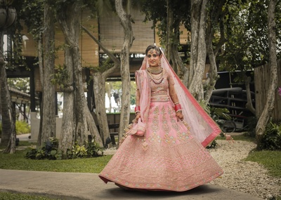 The pretty bride in a pink lehenga for her wedding