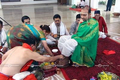Groom performing wedding rituals dressed in white dhoti and green silk Angavastram