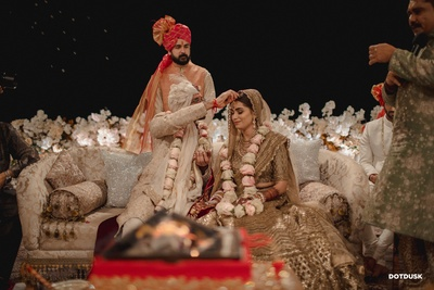 The groom putting sindoor on the bride's forehead during the sindoor dana ceremony.