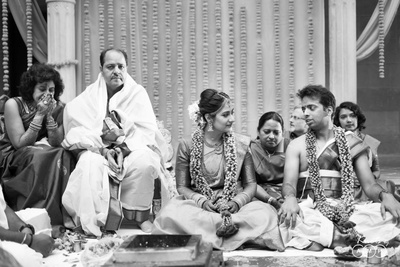 The couple and their families sit asround the havan kund during the wedding ritual.