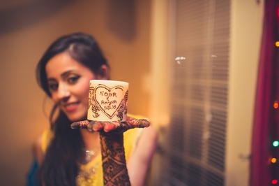 The bride draws out a heart with the couple's name on a candle