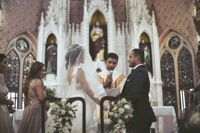 The couple taking their wedding vows in the church