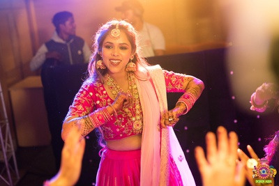 Candid shot of the bride dancing at her mehendi ceremony