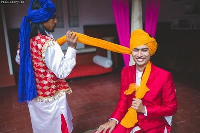 Blood red sherwani paired with white pants and bright yellow safa for the wedding ceremony.