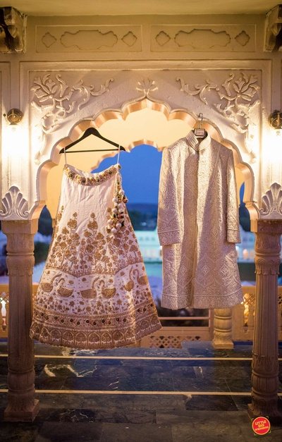 The ivory lehenga and ivory sherwani of the bride and the groom