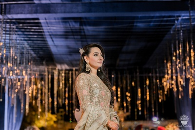 Adorable bride in a beige Anarkali suit at her Sangeet ceremony