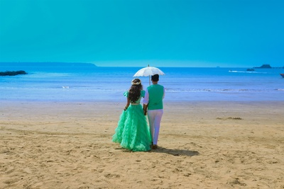 The bride and groom taking a walk on the beach, enjoying every moment to the fullest!