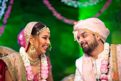 Candid capture of the bride and groom at the wedding mandap