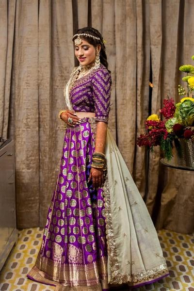 The bride looks stunning in this purple and gold lehenga for the Bhajan Sandhya.