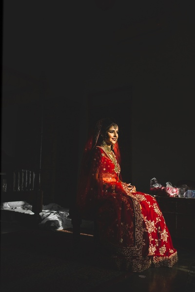 the bride looking beautiful in a red lehenga for her wedding