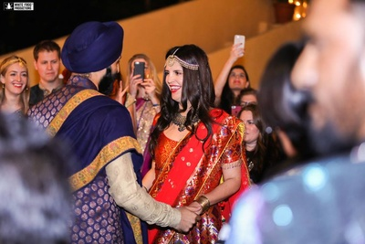 Dressed up in complementing purple and red colored outfits for sangeet ceremony held in Samode palace, Jaipur.