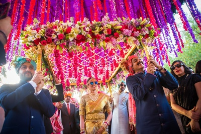 cool bride entering the wedding ceremony under the floral chadar
