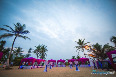 The Leela, Goa wedding venue decorated with magenta cabanas blue bolsters and white covers of table stands