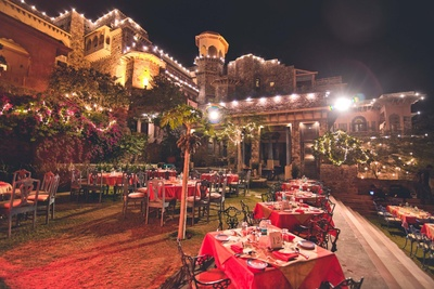 Neemrana Fort Palace hosting the wedding of a beautiful couple with a red and gold themed reception ceremony