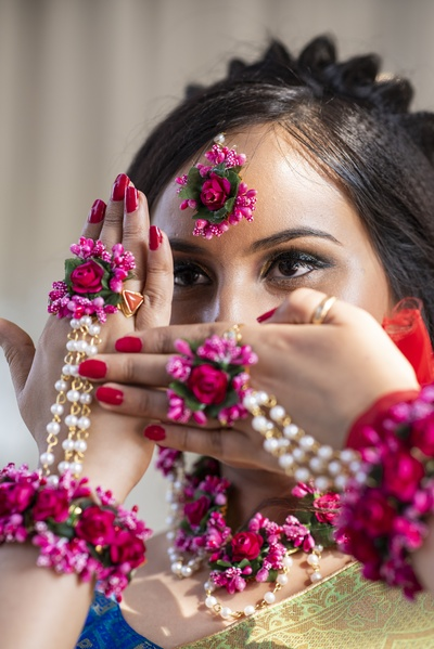 The bride flaunting her red, purple and gree floral jewellery attached to tiny pearl strings.