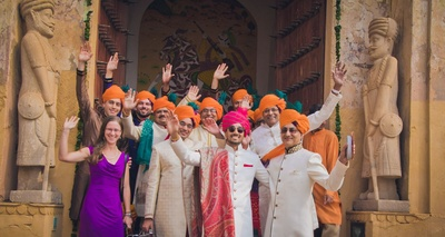 All baraatis dressed in kesari and blue safa, while the groom is standing out in a pink leheriya safa