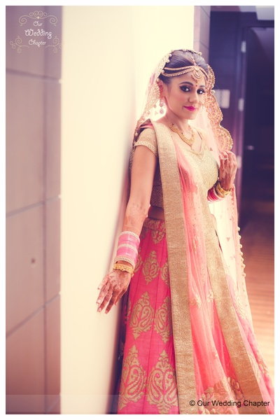 Bubblegum pink and gold customized lehenga styled with gold necklace set and mullti-strand maatha patti by Tanishq