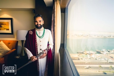 The groom in an ivory sherwani and velvet shawl for his wedding