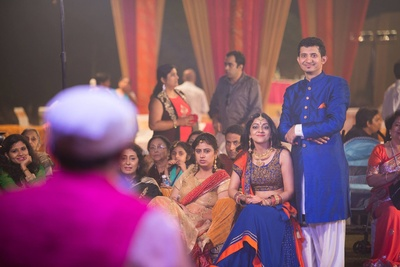 Groom decked in a royal blue achkan with gold button detailing and dhoti pants