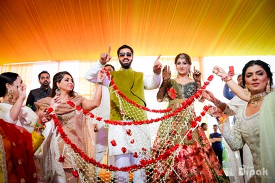 bride and groom having fun at the mehndi ceremony