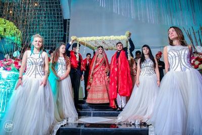 The bride entering the wedding venue with a phoolon ki chaadar over her.