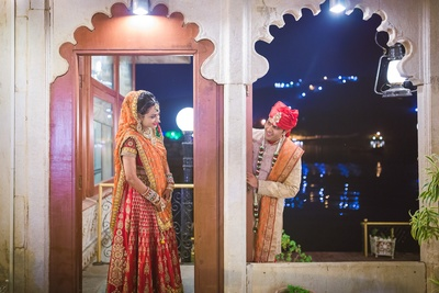 Red orange and green mix-matched wedding lehenga featuring sequins, embroidered motifs and gold laces