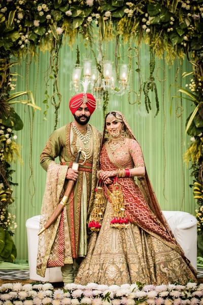 The bride and groom look stunning while striking a pose against a whimsical green-hued decor!