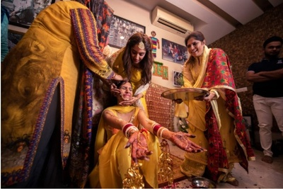 The bride's family putting some haldi on her face at the haldi ceremony.