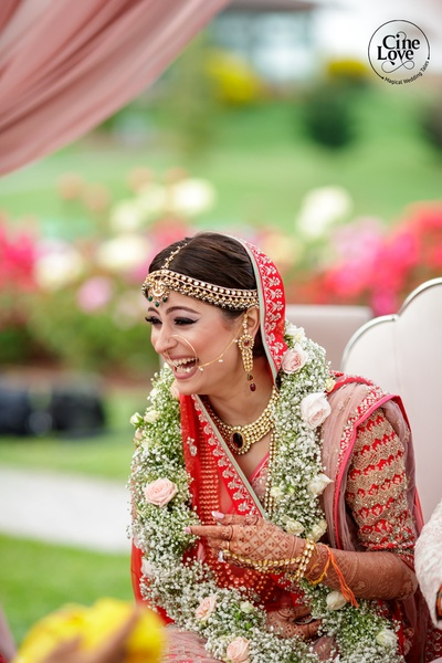 The bride flaunts an unconventional jaimala made of baby breaths and pink roses.
