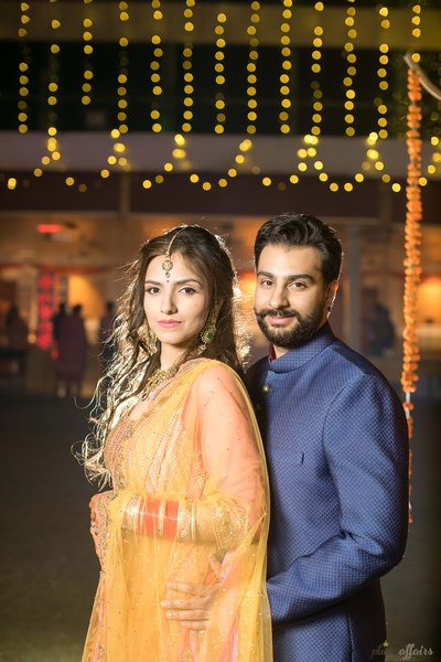 Bride and groom pose together in contrasting outfits during the mehndi function