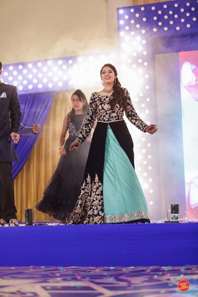 Bride wearing front slit mint blue and black anarkali with heavy gold zardozi work.