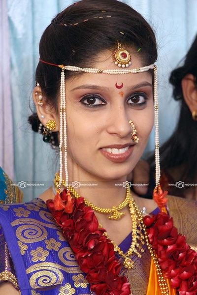 Bride looking ravishing in finely done eye liner styled with gold ear tops