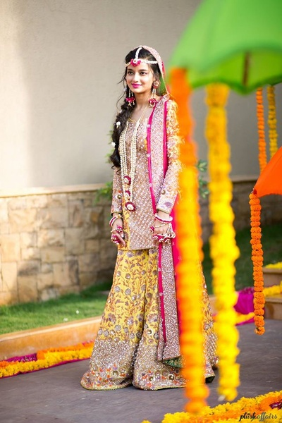 Dressed up in yellow sharara paired with a pink dupatta for mehndi ceremony.