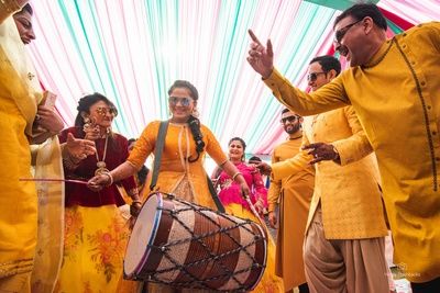 Everyone is having a gala time as the bride starts playing the dhol!
