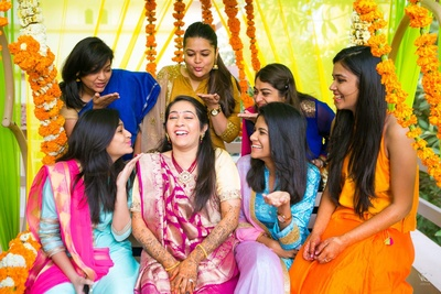 Bride and bridesmaid dressed up in colorful ethnic outfits having fun at Mehendi ceremony held at home