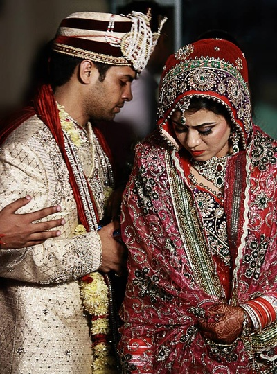 Bride decked in red embellished saree beset with a furbished dupatta