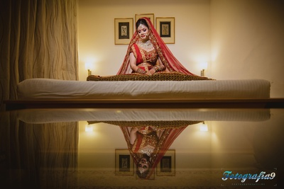 Red bridal lehenga embellished with gold zari worked motifs, styled with polki studded heirloom necklace set