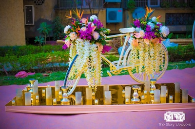 Outdoor mehndi decor props - white bicycle laden with fresh flowers kept on a reflective golden glass with candles