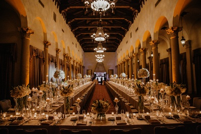 The reception decor looks extravagant, with white florals, candles, and exquisite crockery.
