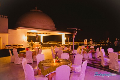 Gold table covers with moroccan lamps and clustered fresh flowers for clustered dinner setting at Jagmandir, Udaipur