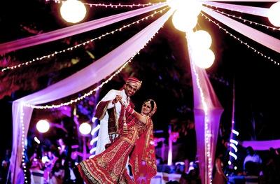 Wedding decor set up with white lanterns, pink and purple drapes, illuminated by fairy lights