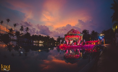 Outdoor poolside wedding mandap decorated with floral arrangement, kalires and clustered floral arrangement