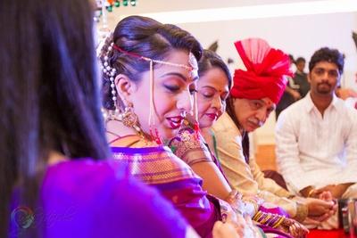 Twisted bridal updo styled with an ethnic beaded Mundavlya