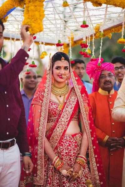 Bride Nitisha's entry for the wedding ceremony under phoolon ki chaadar.